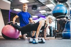 Woman working out on a ball with personal trainer. Stock Image