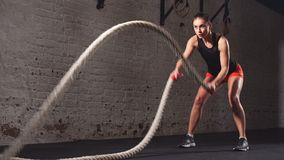 Woman working out with battle ropes in the gym.  stock video footage