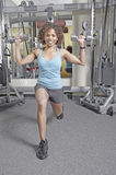 Woman working out with Dumbbells. African American woman working out in a gym doing lunges and holding dumbbells up at her shoulders Stock Photography