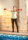 Woman working out with dumbbells at fitness club Royalty Free Stock Photos