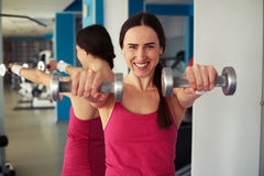 Woman is working out with dumbbells in gym near mirror Stock Photo