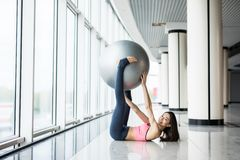 Woman working out with exercise ball in gym. Pilates woman doing exercises in the gym workout room with fitness ball. Fitness woman doing exercises for muscle royalty free stock images