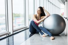 Woman working out with exercise ball in gym. Pilates woman doing exercises in the gym workout room with fitness ball. Fitness woma Stock Photo