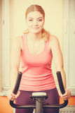 Woman working out on exercise bike. Fitness. Stock Photos