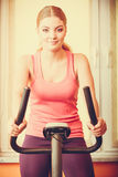 Woman working out on exercise bike. Fitness. Royalty Free Stock Images