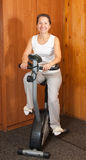 Woman working out on exercycle at home Royalty Free Stock Image