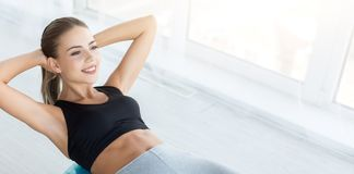Woman working out with fitness ball in gym. Making beautiful belly. Smiling woman working out with fitness ball, doing exercises for muscle press, panorama, copy royalty free stock image