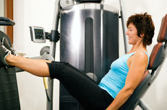 Woman working out in gym. Mature woman working out in gym on a leg machine Royalty Free Stock Images
