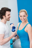Woman working out in a gym with dumbbells Stock Image