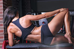 Woman working out in the gym. Rear view of a toned young woman working out in the gym Stock Image