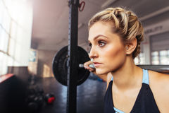 Woman working out at the gym using weight bar. Stock Photo