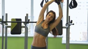 Woman working out in gym warming up her upper body and hands. Healthy lifestyle concept. Slow motion stock video footage
