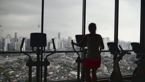 Woman Working Out in Gym. Young woman working out hard in sports club.Attractive girl at the gym riding on the spinning bike with great view over city.Active stock video footage