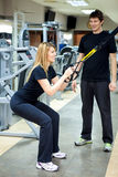 Woman working out, her personal trainer helping her Royalty Free Stock Photos