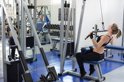 Woman working out on lat machine. Beautiful and  young woman in motion working out in the gym on lat machine Stock Photo