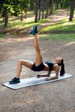 Woman working out on park on summer afternoon doing fit exercise on gray mat, with left leg high. royalty free stock images