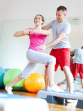 Woman working out with personal trainer. Young couple working out at the gym Royalty Free Stock Photography