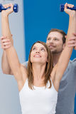 Woman working out with a personal trainer stock photography