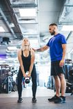 Woman working out with personal trainer at a gym. Stock Photography