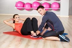 Woman working out with a physical trainer. Slender fit young women working out with a handsome male physical trainer at the gym toning her abdominal muscles Royalty Free Stock Images