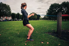 Woman working out with resistance band in the park. A young woman is exercising and working out with a resistance band in the park Stock Photo