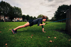 Woman working out with resistance band in the park Stock Photos
