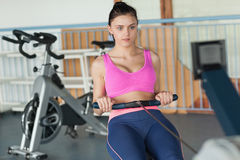 Woman working out on row machine in fitness studio Royalty Free Stock Image