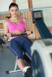 Woman working out on row machine in fitness studio Stock Photography