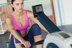 Woman working out on row machine in fitness studio Royalty Free Stock Photo