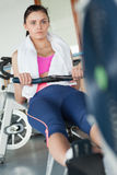 Woman working out on row machine in fitness studio Stock Photo