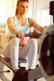 Woman working out on row machine in gym Stock Photo
