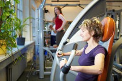 Woman working out on rowing machine Royalty Free Stock Images