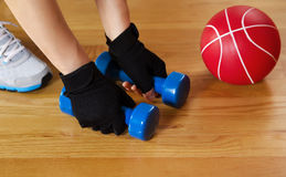Woman working out with small weights on wooden gym floor. Horizontal image of female hands wearing workout gloves while lifting small weights off of wooden gym stock images