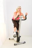 Woman working out on spinning bike Stock Images
