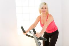 Woman working out on spinning bike Royalty Free Stock Photos