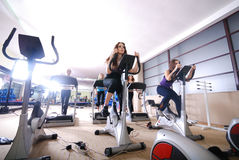 Woman working out on spinning bike at gym stock photo