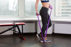 Woman working out in the studio. Beautiful young woman working out in the studio with elastic band Royalty Free Stock Images