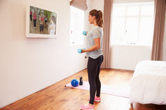 Woman Working Out To Fitness DVD On TV In Bedroom Stock Photography