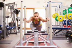 Woman working out using equipment at a gym Stock Image