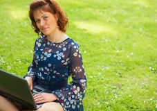 Woman working outdoors. Young woman using her laptop outdoors Stock Images