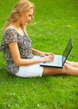 Woman working outdoors. Young woman using her laptop outdoors and sitting on a grass Royalty Free Stock Photography