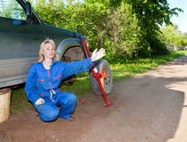 The woman in working overalls tries to replace a wheel at an off-road car, and asks the help Stock Photos