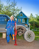 The woman in working overalls tries to replace a wheel at an off-road car Stock Photography