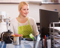 Woman working on PC. Blonde woman in apron working on PC at kitchen Royalty Free Stock Photography