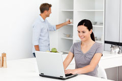 Woman working on the pc in the kitchen royalty free stock image