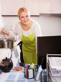 Woman working on PC. Smiling blonde woman in apron working on PC at kitchen Stock Images