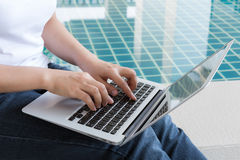 Woman working with PC. Woman working with tablet sitting at swimming pool Royalty Free Stock Images