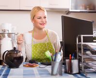 Woman working on PC. Young blonde woman in apron working on PC at kitchen Stock Photo