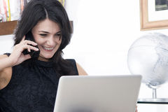 Woman working with phone and laptop Royalty Free Stock Photo