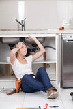Woman working in the pipe of the kitchen Stock Photography